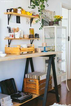 Ateliê de cerâmica têm mesa de pinus com cavaletes pintados de preto.