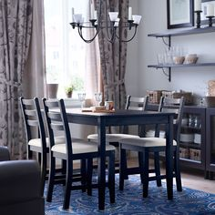 ikea - A black-brown dining table and chairs with beige seat cover