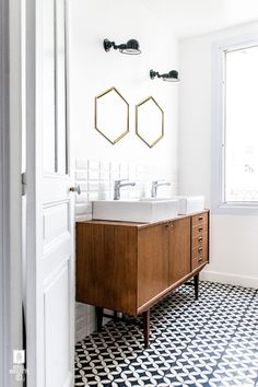Loving the tile floors and unique mirrors in this super chic bathroom.