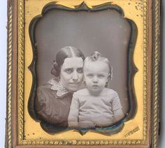 """Sixth plate daguerreotype of mother and child in cheek-to-cheek pose, both positioned low in mat as if peeking over its bottom edge, by Benjamin Franklin Upton. Brass mat stamped """"Upton"""" lower right. Housed in a half case."""