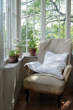 White porch room with potted geraniums in terracotta