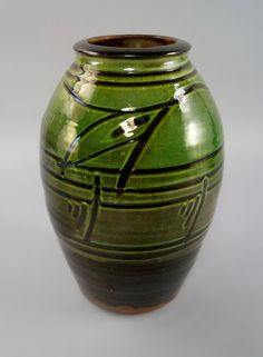 Michael Cardew OBE, British, 1901-1983, a tall green slipware Wenford Bridge earthenware vase, decorated with horizontal bands with slashed motifs, seal marks to base, 29cm high.