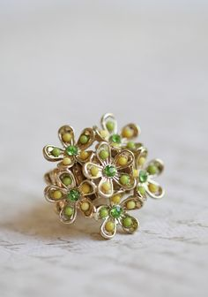 Grace Gardens Bouquet Ring shopruche.com. Cheerful flowers bloom on this gold colored ring. Each flower is adorned with sparkling green rhinestones and yellow beaded detail. Elasticized band.