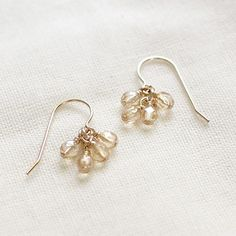 On these gorgeous little earrings, a cluster of translucent glass champagne-colored beads dangle from 14k French gold-filled earwires.  + measures just under 1 from the top curve of the earwire to the base of the earring + gold-filled earwires, glass beads + packaged in a lovely small gift box tied with black ribbon  International customers, please be familiar with your countrys taxes/duties before ordering. Washington state orders will incur a 9.5% sales tax.