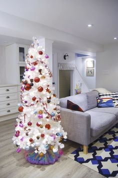 """The slim, snowy Treetopia Basics white tree brightened up Jennifer of Rambling Renovators' basement. Meant to be a """"kid's tree"""", she decorated it with bold colors and handmade crafts."""