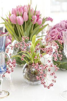 Sobre o centro da mesa, rosa, tulipas, callas, rosas, micro orquídeas, e mini orquídeas phalaenopsis, em tons variados de rosa, foram dispostos por Marcinho Leme da Milplantas em vasos de cristal de diversos tamanhos e modelos da Coleção Santorini, com lapidação de bolhas, da Tania Bulhões.