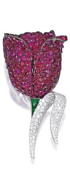 18 Karat White and Blackened Gold, Ruby, Diamond and Emerald 'Tulip' Brooch, Michele della Valle. Designed as a voluminous tulip blossom, the petals set with numerous round and oval-shaped rubies weighing 86.15 carats, the leaf set with single-cut diamonds weighing 5.30 carats, completed by a stem set with three emeralds weighing 2.05 carats, signed Michele della Valle, numbered 150753.
