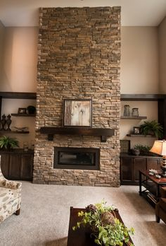 Floor to ceiling stone surround gas fireplace with custom shelving. Parade of Home #11 - Homestead