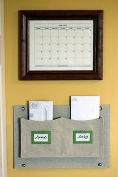 Calendar in front of glass to write on.  Pockets below for bills.