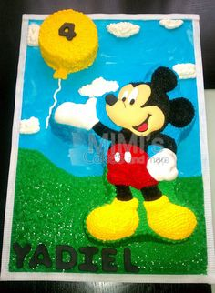 MIckey Mouse cake in frosting.  The sky, clouds and grass are also made in frosting.
