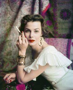 Lillian Marcuson wearing a gold arm cuff. Photographed by Milton Greene in Weston, Conn., 1954.