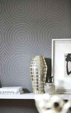 An all over wallpaper design featuring a repeated design of spiralling circles, with shimmering metallic detailing.