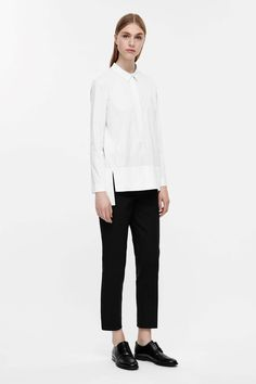 Made from a soft cotton-blend with stretchy finish, this A-line shirt has a split front and a partial button fastening. Designed to slip-on, it has long sleeves, a narrow grosgrain collar and ribbed detail finishes.