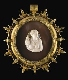 A CARVED OVAL ONYX CAMEO BUST OF A WOMAN 16TH CENTURY Bare-breasted, with elaborate coiffure and diadem, holding a fluted bowl of fruit, facing front and turned slightly to the right; in an oblong gold mount; applied to an oval grey agate ground within a later silver-gilt oval frame with suspension loop.
