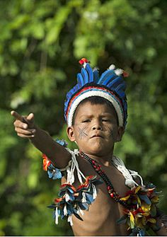 A boy from the Paresi tribe slings a rock while playing in the Kari-Oca village, where indigenous groups are staying during Rio+20 conference in Brazil.