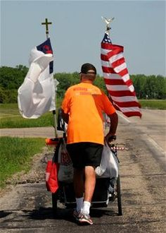 Walking cross-country to raise $50,000 for wounded and disabled veteran programs, military veteran Sgt. Chuck Lewis travels near Grand Forks Air Force Base, N.D. June 13, 2013. Lewis carries everything he needs on his cart necessary to set up camp where available along the way to the Vietnam Veterans Memorial wall in Washington, D.C. (U.S. Air Force photo/Airman 1st Class Ashley Nicole Taylor)