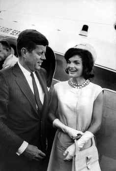 Senator John F. Kennedy being greeted by his wife Jacqueline, wearing a silk-linen sheath dress & her signature pillbox hat.