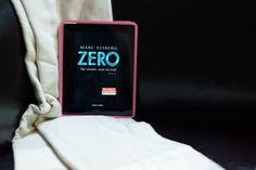 Titelseite von Marc Elsbergs Zero auf dem I Pad mit pinker Hülle auf schwarzem Sessel mit Decke von Elmas Home