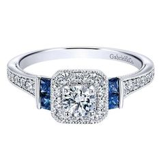 """14K White Gold .56cttw Vintage Diamond and Sapphire Halo Engagement Ring. This ready to wear diamond engagement ring, features .56cttw of round diamonds with bead set side round diamonds. The center diamond is a .24ct G/SI2 round brilliant accented by a square shaped halo. There are also .21cttw of square """"A"""" quality blue sapphires outside the halo. All side diamonds are G/SI quality to perfectly match the center diamond. Price is for completed ring, including center diamond. Designed by…"""