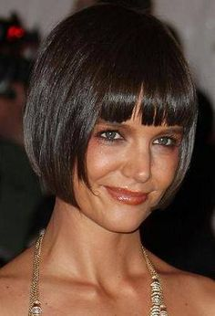 Jaw length bob. Slightly shorter in the back with subtle layering throughout. Bangs completely blunt and straight and cut just above the eyebrow. Ask for longer, sideswept bangs if you have a slightly round face. Need a good flat iron for this look.