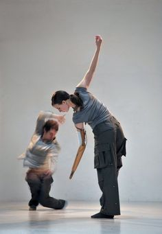 Candoco Dance Company (London, UK). Image description: two dancers from integrated dance company, Candoco. They both wear cargo pants and grey shirts. The woman in the centre of the picture is leaning over, looking down towards the floor. Her arms are held in almost a straight light from floor to ceiling. Her lower arm is a prosthetic, without a hand. Behind her on stage, a male dancer is a blur of movement. He crouches just above the ground, his knees together, with one arm above his head.