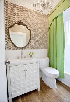 love the valance and shower curtain combo...love the shape of this mirror the patterned wall and the cabinet...such a cool little bathroom.