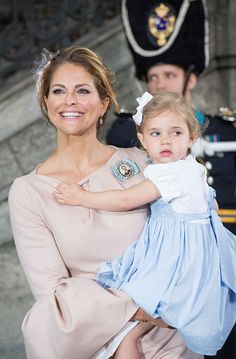 Princess Madeleine of Sweden holds Princess Leonore as they leave the christening of Prince Oscar at the Royal Chapel in Stockholm on May 27, 2016.