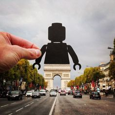 Cut paper artist Rich McCor (aka @paperboyo) creates small silhouetted shapes and brings them to life by holding them against European monuments.