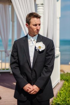 This White Phalaenopsis Orchid boutonniere matches the bride's bouquet.  Photography by http://www.luxlightphotography.net/