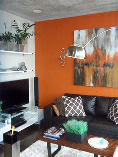 Currently cursed with a similar sofa, I love how modern the orange walls makes it feel.
