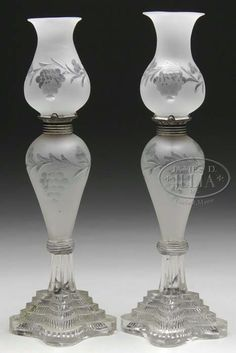 Matched pair of Sandwichv Glass whale oil lamps, burners and shades. Lamps have a blown font,  frosted throughout with grape and vine decoration. Collars are pewter and original to the lamp. Base is a pressed five step base, The shades matching the lamp in pattern and form and frosted throughout with a grape and vine decoration. A rare and complete pair of sandwich glass. Massachusetts, circa 1830-1870