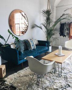 deco salon bleu canard, grand salon avec les murs gris, un sofa bleu, miroir mural rond et tapis berbère