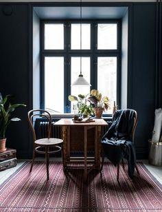 Dining Table Near Window With Dark Blue Wall