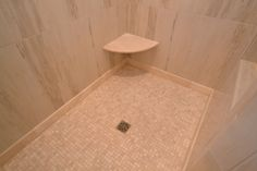 Master shower with corner bench and mosaic tile floor.