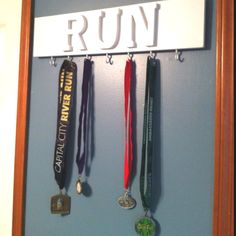 "24"" board, cup hooks, block letters + gorilla glue and spray paint = race medal hanger!"