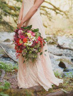 Handmade pink wedding dress with a vibrant, cascading bouquet