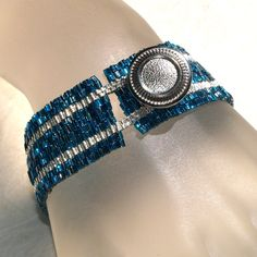 Silver Stripe in Blue Zircon Band...  Peyote bracelet created from silver-lined triangle beads and galvanized silver delicas, with a vintage button closure.  I love the button - reminds me of a hubcap.  :-)  $33