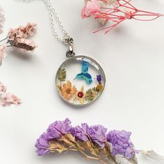 This alluring necklace is made from pressed and dried flowers plus a beautiful colour changing laser cut bird. Handmade with love by our very talented #featureddesigner Florifying Moments. ~*~ #florifyingmoments #australianartist #australianartists #australiandesigner #resinflower #resinflowers #resinart #resin #resinartist #resinartwork #resincrafts #resincasting #resinpour #makearteveryday #resincraft #resinjewellery #resinnecklace #designerspotlight #meetthemaker Resin Necklace, Resin Jewelry, Pendant Necklace, Handmade Jewellery, Handcrafted Jewelry, Unique Jewelry, Resin Flowers, Dried Flowers, Pot Lights