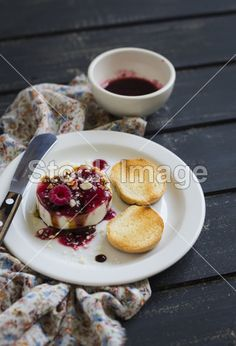 Sheep cheese with berry sauce, nuts and balsamic vinegar on a dark surface