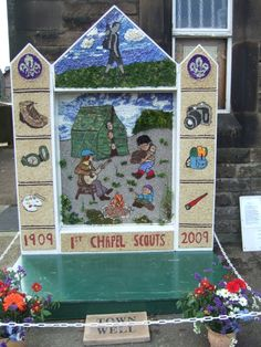 Town Well decorated for the 2009 season. Chapel-en-le-Frith.       The theme for the well-dressing was the centenary of the 1st Chapel Scouts.