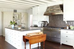 Great use of dark backsplash slab.  Also love the apothecary chest style island and the drop leaf table at the end of the island!  1_dodson-interiors-whitekitchen