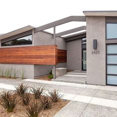 Love the horizontal natural tone wood siding mixed with the gray stucco walls and glass garage door.