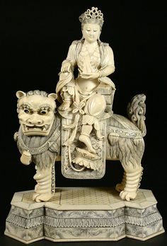 """Ivory Carving, Guanyin on Foo Dog, 20th C. - Carved from a massive tusk th main part of this sculpture is one piece of ivory measuring 8.75"""" wide. Featuring Quan Yin sitting astride a Foo Dog and holding fire in her hand while her footrests on a lotus leaf. Intricate detailing of the fur and saddle shows floral details. The 'floor' of this piece is scribed to resemble patterning. Dynasty seal carved on the bottom of the base."""