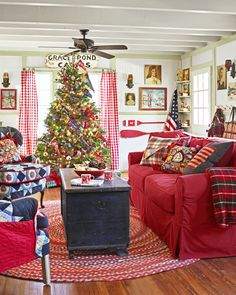 """The year-round use of red in the living room takes inspiration from the words of Charles Dickens: """"I will honor Christmas in my heart, and try to keep it all the year."""" The tree is peppered with pennants from National Parks and roadside attractions"""