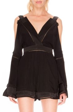 A cold-shoulder design and insets of open stitching put a daring twist on this breezy romper styled with bell sleeves and a skin-baring exposed back.
