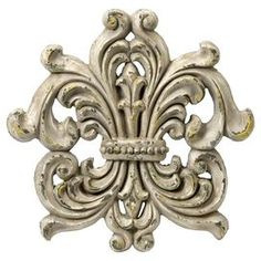 Wall plaque in aged cream.    Product: Wall décor   Construction Material: Polyurethane     Color: Aged cream   Features: Fleur-de-lis design    Dimensions: 18.5 H x 18.5 W x 2 D