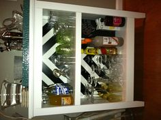 Bookshelf bar. Bookshelf from Target, I taped a chevron with blue tape and black spray paint, add glasses etc and done!