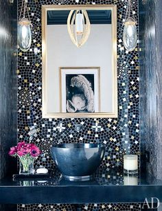 A custom-made glass- tile wall treatment created by Drake and Cheryl Hazan Mosaic animates the powder room; the hanging light is by Porta Romana, the sconces are by Jonathan Browning Studios from Holly Hunt, and the sink fittings are by Drake for THG