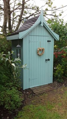 My cottage garden pretty little corner shed little summer house. Hand made bespoke garden shed.  Painted with cuprinol. Curved concave wooden roof. Driftwood heart shaped wreath on shed door.