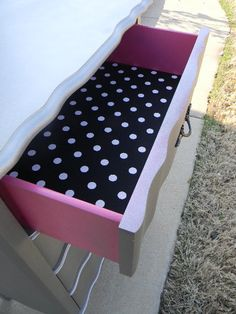 Paint the outer and inner sides of a dresser along with some pretty wrapping paper as a bottom.